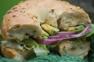 Make a Southwestern veggie bagel sandwich with red onion, lettuce, avocado and jalapeno cream cheese.
