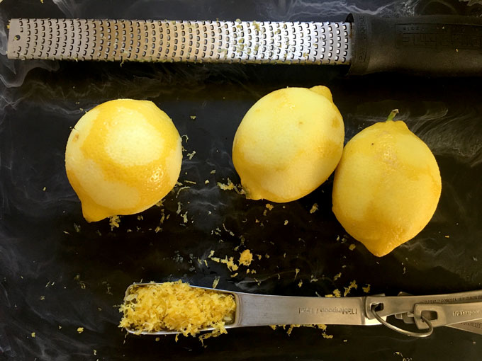 three lemons on a black marble background with a tablespoon full of zest and a microplane zester above the lemons