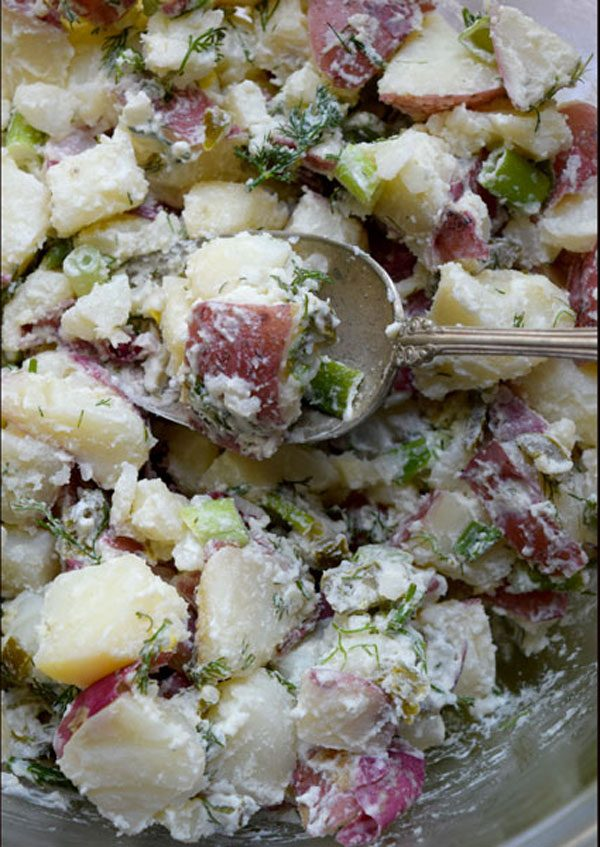 bowl of potato salad with dill, jalapeno and chives with silver spoon