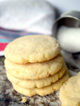 stack of sugar cookies with kitchen towel in background