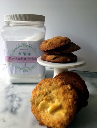 cookies on a small white pedestal with a container of allulose sweetener in background