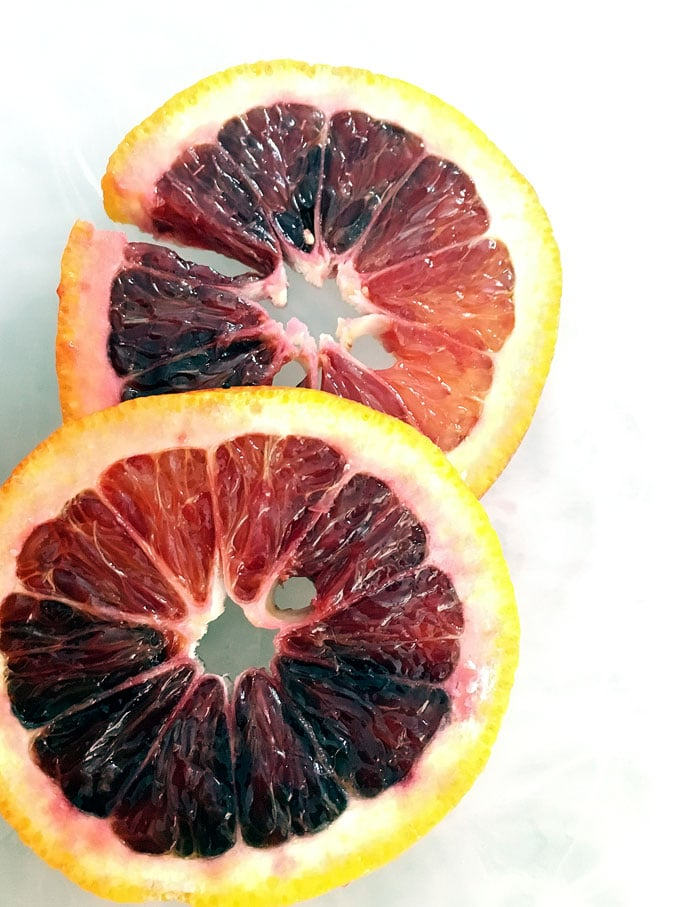 two slices of blood oranges on a white counter