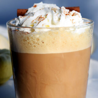 glass containing a pumpkin drink topped with whipped cream and a cinnamon stick