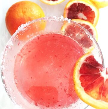 cut blood oranges placed around a mixed drink of blood orange juice and vodka